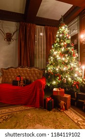 gifts at the Christmas tree. Christmas evening by candlelight. classic apartments with a fireplace.