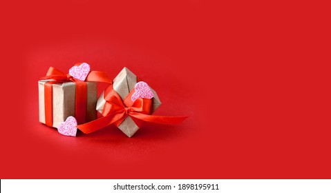 Gifts  and decor hearts  on red background. Minimalist concept for Valentines day Mothers day, Women day or wedding. Greeting banner with copyspace. - Shutterstock ID 1898195911