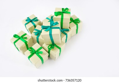 Gifts, festive decor. Capsules with green ribbon on white background.