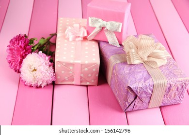 Gifts and flowers, on bright wooden background
