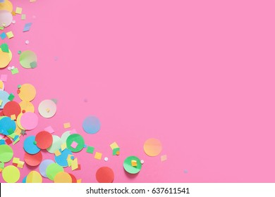 Gifts, garland, festive decor and confetti. Pink background.