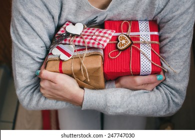 A lot of gifts on Valentine's Day in the hands of a girl