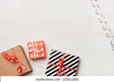 Gifts on white wooden background. Christmas background.