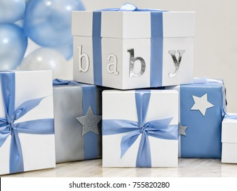 Gifts and presents for a new baby boy with baby blue ribbons and balloons with copy space
