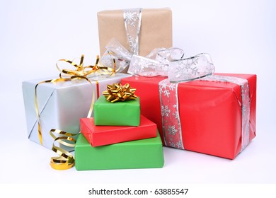 Gifts in silver, green, brown and red wrapping with bows on white background