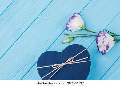 Gifts for valentines day for girlfriend. Blue heart shaped box and lisianthus eustoma flowers. Blue wooden table background.