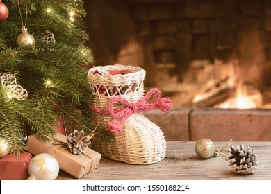 Gifts and whisker stocking under the Christmas tree in the room with a fireplace on Christmas eve.