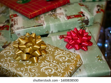 Gifts wrapped in Christmas themed wrapping paper, decorated with ribbon