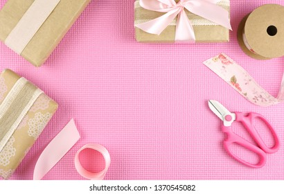 Gifts wrapped in kraft paper and pink ribbons overhead flat lay for Mother's Day, birthday or Valentine's Day celebrations, with copy space.