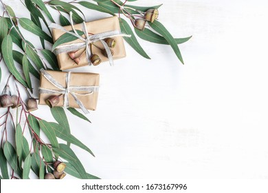 Gifts wrapped in natural paper with silver ribbon and rustic twine surrounded by eucalyptus leaves and gum nuts on a white background. Gifts for, Birthday, Christmas, Mothers and Valentines Day.