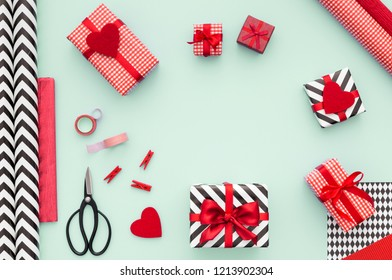Gifts wrapped in red paper on a mint color table. Flat lay. Christmasnor New year gift packing. Holiday decor concept.