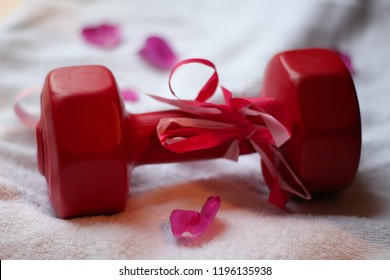 Gift-wrapped dumbbell with rose petals