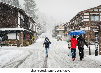 Gifu, Japan - Dec 5, 2017. In the winter snow is heavy,female tourist holding transparent umbrella and walking on the street with background of Ancient houses and shop of Shirakawa-go at Gifu, Japan.