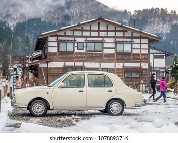GIFU, JAPAN - NOVEMBER 25 : Walking street with tourists and vintage white car in Shirakawa village in early winter season with snow under cloudy sky in Gifu, Japan, on November 25 ,2017.