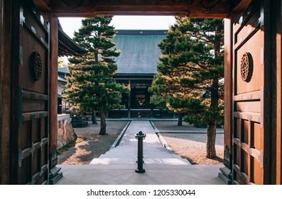 Gifu, JAPAN - Old historic ancient Japanese wooden main hall Shinshu-Ji temple of Hida Furukawa old town. Shot through wooden old gate with evening light
