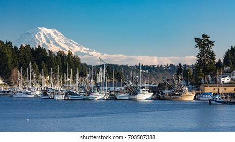 GIG HARBOR, WASHINGTON, DECEMBER 7, 2013: Commercial fishing vessels sit idle, as unusually cold weather causes ice to form in the harbor, with Mt. Rainier in the background. EDITORIAL USE ONLY.