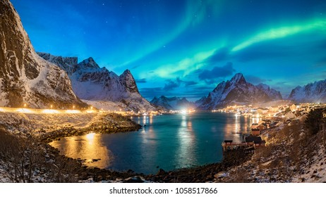 giga panorama with green northern lights over the fishing village of reine on  lofoten islands in norway snow covered mountains winter landscape and city lights