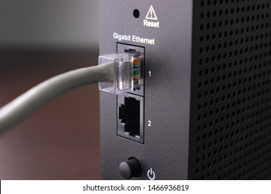 Gigabit LAN Ethernet (RJ45) cable connected to a WiFi router repeater.