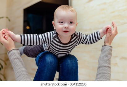 Giggling baby in striped shirt up on knees of adult who is holding her hands to simulate flying
