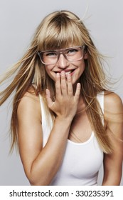 Giggling blond woman in glasses, portrait