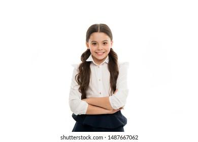 A giggling schoolgirl. Adorable little schoolgirl with happy smile keeping arms crossed. Small schoolgirl looking nice in school uniform. Cute schoolgirl with long brunette hair and charming look.