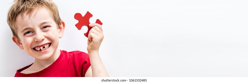 giggling toothless 7-year old child enjoying finding a piece of jigsaw for concept of fun education, growing up difference or idea for child healthcare, copy space white background