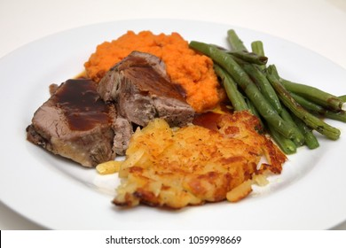 gigot with swiss hash browns, mashed carrots and beans