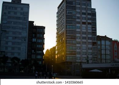 Gijon, Asturias, Spain; 09/26/2018: Orange sunrays through two buildings in a sunset in Gijon, Asturias, Spain