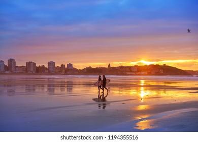 GIJON, ASTURIAS, SPAIN - JUNE 6: San Lorenzo beach sunset with surfers in Asturias on June 6, 2017 in Gijon, Asturias, Spain