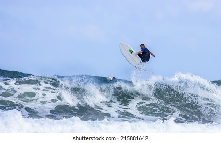 GIJON, SPAIN     August 31 2014:  Young athletes surfing on a beach located on the outskirts of Gijon. Spain. August 31, 2014