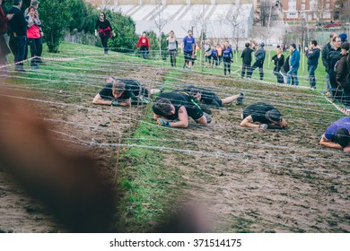 GIJON, SPAIN - JANUARY 31, 2016: Farinato Race event, a extreme obstacle race, celebrated in Gijon, Spain, on January 31, 2016. Participants crawling under a barbed wire in a test of the race.