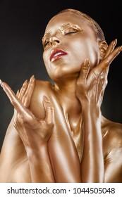 Gilded body. Golden makeup. Woman with golden makeup and bodyart