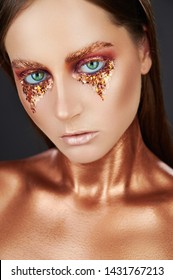 Gilded body. Golden makeup. Woman with golden makeup and bodyart. High fashion model