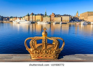 Gilded crown on Skeppsholmsbron with Stockholm Old Town in the background