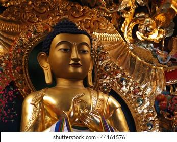 gilded metal statue of preaching Buddha in a Tibetan Buddhist monastery in Sarnath, India