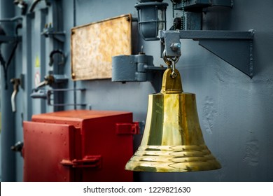 gilded old bell hanging aboard a warship. yellow bell on a warship.