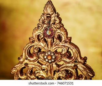 Gilded wood carving decorated with glass mosaic and paste. Part of oriental religious related object. Golden background.