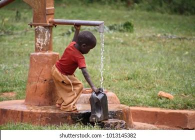 Gilgil, Nakuru County Kenya, November 23 2017, small child filling a jug of water from the local school well. Many families do not have access to clean water at home and carry it for long distances.