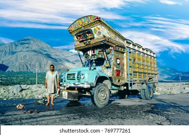 GILGIT, PAKISTAN - AUG 6, 1987: proud truck driver presents his painted truck at the karacorum highway in Pakistan. The Karakoram highway connects Pakistan with China.