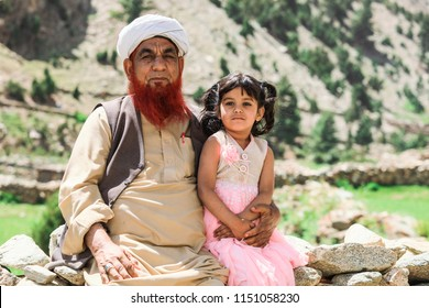 Gilgit, Pakistan - June 10, 2018: Old Pakistanian Man in Traditional Pakol with Little Granddaughter
