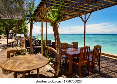 GILI AIR, INDONESIA - February 2020: Cozy beach lounge cafe with wooden furniture and umbrellas on Gili Air, Bali, Indonesia