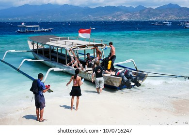 GILI TRAWANGAN, INDONESIA -- OCTOBER 14 2007: Divers boarding a wooden outrigger dive boat from the beach of Gili Trawangan Island Indonesia