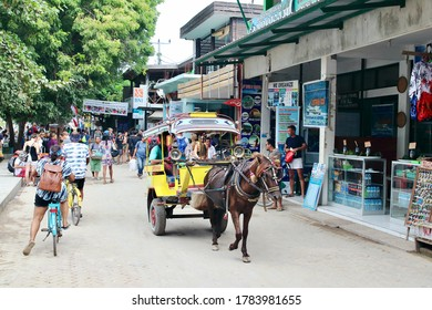 Gili Trawangan, Lombok, Indonesia - August 12th of 2019: Tourists, locals, bicycles, carriages,  and horses mixed in the sand promenade that rounds the largest Gili Island.