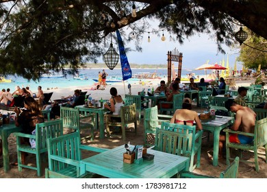 Gili Trawangan, Lombok, Indonesia - August 12th of 2019: Tourists have a meal or take a bath in the amazing spot of the harbor beach of the largest Gili Island.