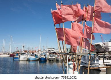 GILLELEJE, ZEALAND, DENMARK - AUGUST 14, 2107: Fishing boats and red flags flying in wind in harbour of fishing town on the Kattegat Coast