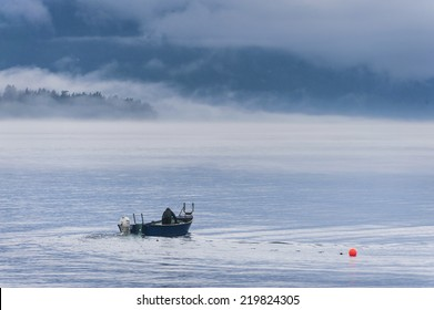 Gillnet Salmon Fishing. A gillnetter makes a set in the San Juan Islands drifting for sockeye salmon on a foggy day in the Pacific Northwest.