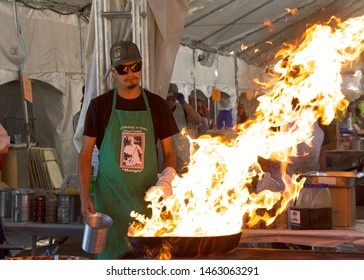 Gilroy, CA - July 27, 2019: World famous pyro chefs putting on spectacular flame up shows while preparing garlic laced calamari and scampi in huge iron skillets at the 41st annual Garlic Festival.