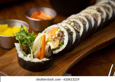 Gimbap (Kimbap) is a Korean dish made from steamed white rice (bap) and various other ingredients, rolled in gim (sheets of dried laver seaweed) and served in bite-size slices.