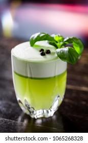gin basil smash cocktail on wooden bar
