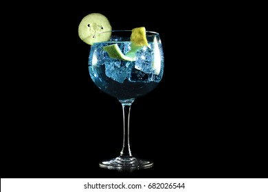 Gin blue tonic with cucumber and lemon on black background